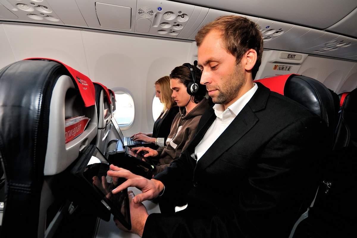 Mobileszközt használó férfi a Norwegian légitársaság egyik gépének fedélzetén. (Fotó: Norwegian Air Shuttle)   © AIRportal.hu