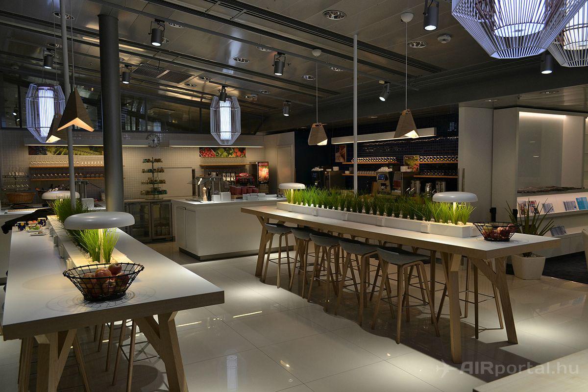 A váró minimalista stílusát néhol zöld dekorációk törik meg, így az étkezőasztaloknál is. Háttérben az italautomaták és a müzlibár látható. | © AIRportal.hu