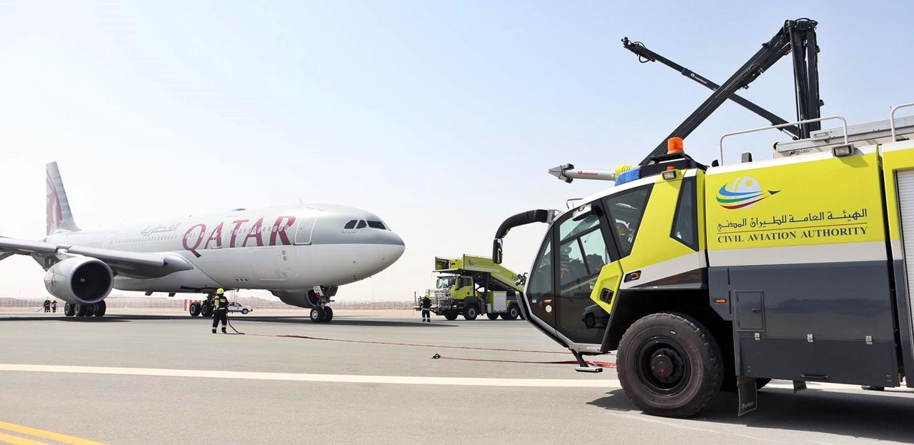 A vészcsúszda nyitása előtti percekben a tűzoltóautók által körbe vett A330-as. (Fotó: Qatar Airways) | © AIRportal.hu