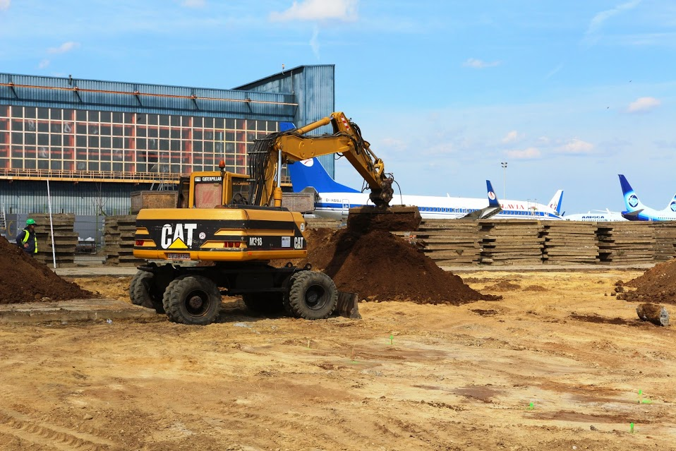 Az új hangárépület építési területe, háttérben az ACE hangárjával és annak előterén parkoló repülőgépekkel. (Fotó: Budapest Airport) | © AIRportal.hu