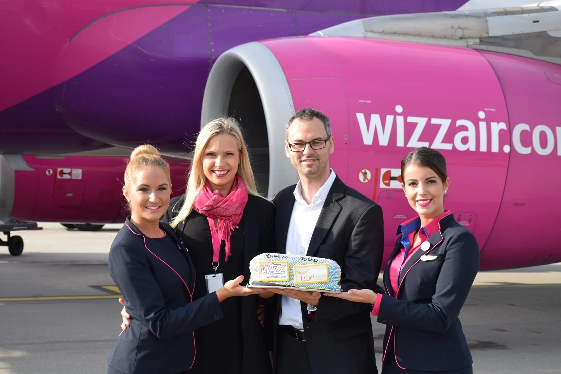 Bogáts Balázs, a Budapest Airport járatfejlesztési vezetője amint átadja a tortát a Wizz Air légiutas-kísérőinek, Tamara Mshvenieradze, a Wizz Air kommunikációs menedzserének jelenlétében. (Fotó: Budapest Airport) | © AIRportal.hu