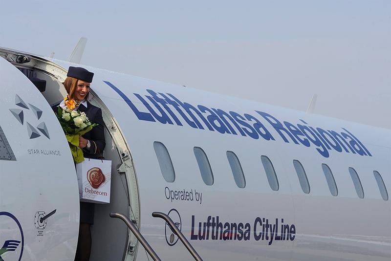 Légiutas-kísérő a Lufthansa Bombardier CRJ900 típusú, Münchenbe induló repülőgépének ajtajában a Debreceni Nemzetközi Repülőtéren 2016. április 11-én. Ezen a napon a német légitársaság elindította menetrend szerinti járatát München és Debrecen között. A járat heti három alkalommal közlekedik a nyári menetrendben. MTI Fotó: Czeglédi Zsolt   © AIRportal.hu