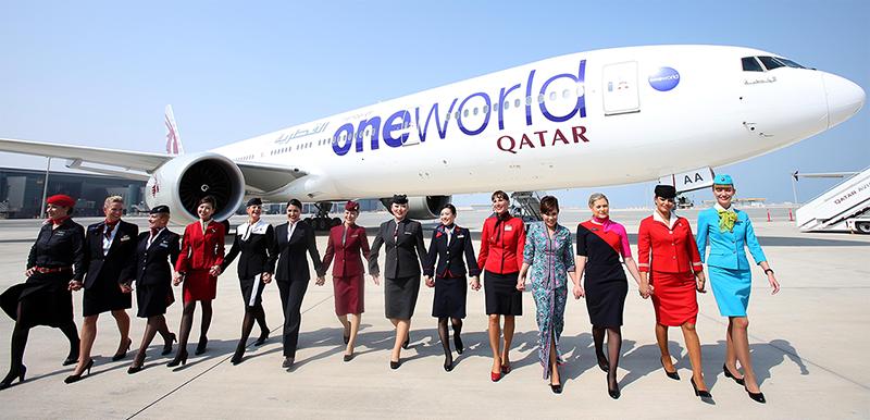 Légiutaskísérők a oneworld tagok formaruháiban a Qatar Airways oneworld festésű Boeing 777-ese előtt. (Fotó: oneworld) | © AIRportal.hu