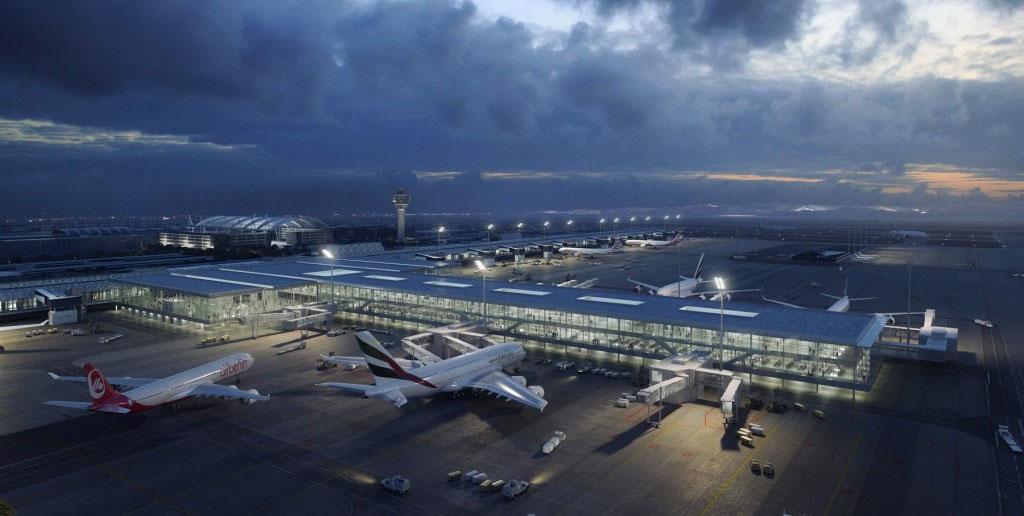 A bővítés látványterve a forgalmi előtér felől nézve, elöl a móló az utashidakkal, a háttérben balra a két terminál közötti Airport Center jól beazonosítható íves tetőzete. (Forrás: Flughafen München GmbH) | © AIRportal.hu