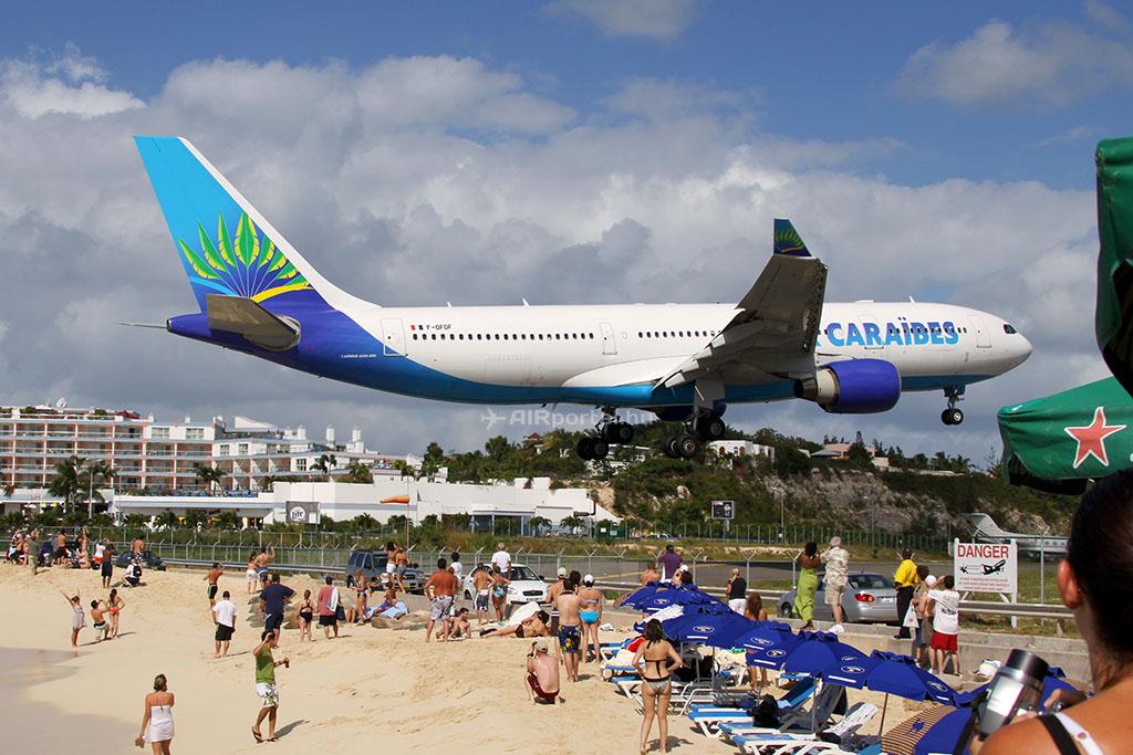 A turistákkal teli Maho Beach látképe a híres Sunset Beach Barból, amint az Air Caraibes Airbus A330-asa leszáll. A kép jobb alsó sarkában jól látszik a veszélyre figyelmeztető egyik tábla. (Fotó: AIRportal.hu) | © AIRportal.hu